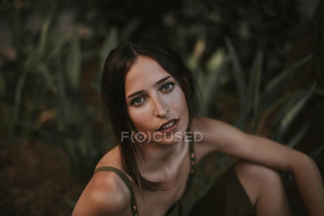 Ritratto di donna attraente in abito kaki seduta a terra e che guarda la macchina fotografica . — Foto stock