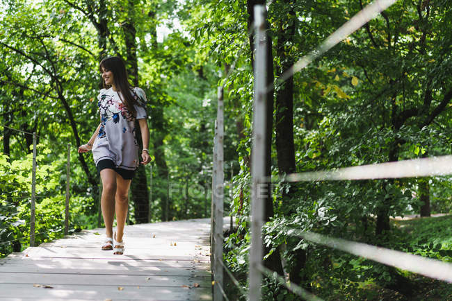 Cheerful woman walking on path in forest — Stock Photo