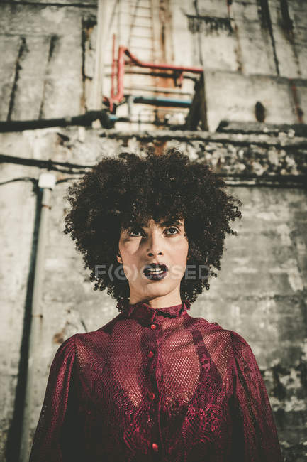 Young woman with volume haircut posing over shabby wall — Stock Photo