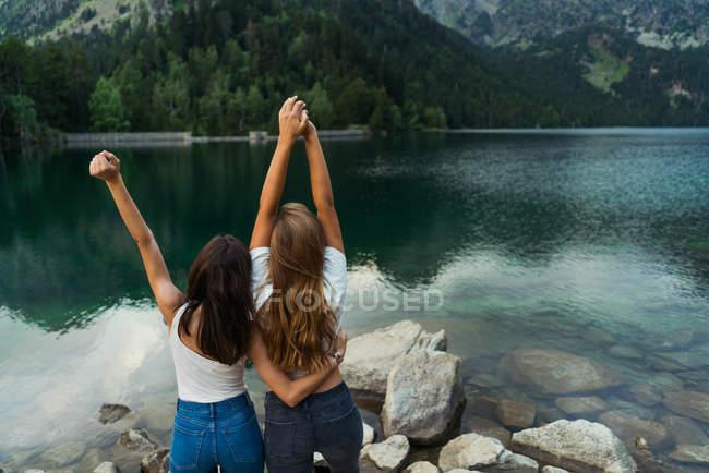 Womenposing at lake shore in mountains — Stock Photo