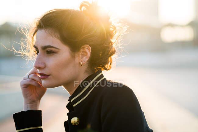 Vue latérale d'une jeune femme portant des vêtements décontractés et de loin à la recherche — Photo de stock