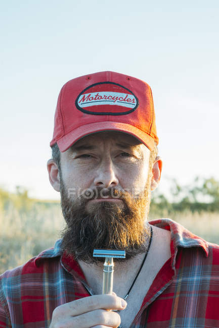 Portrait of bearded man in cap holding double edge razor and looking at camera — Stock Photo