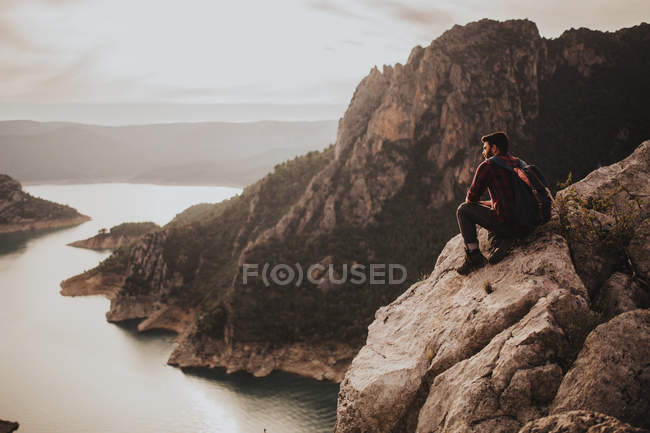 Young traveler admiringdyllic landscape while sitting on rock — Stock Photo