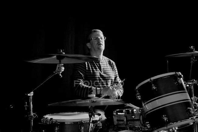 Мужчина в очках, играть на барабанах на стадии — стоковое фото