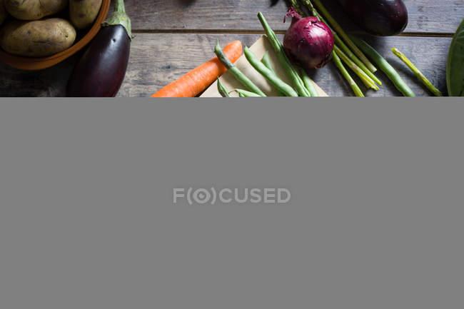 Женские руки режут зеленую фасоль на деревянной доске — стоковое фото