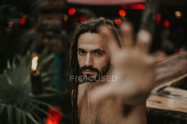 Portrait of man with dreadlocks posing without shirt outstretching hand at camera — Stock Photo