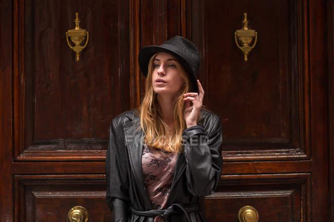 Menina de chapéu olhando para longe enquanto posava contra portas ornamentadas — Fotografia de Stock