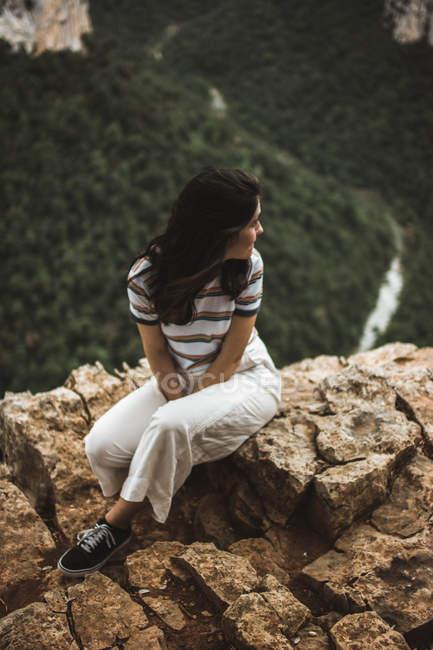 Donna seduta sulla pietra e distogliendo lo sguardo — Foto stock
