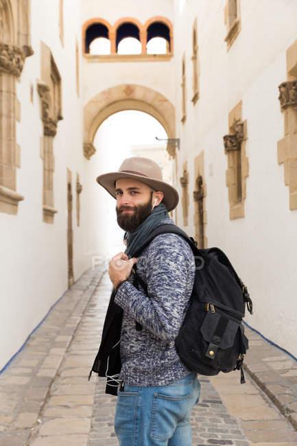 Бородатый мужчина позирует с рюкзаком и глядя через плечо на камеру на улице — стоковое фото