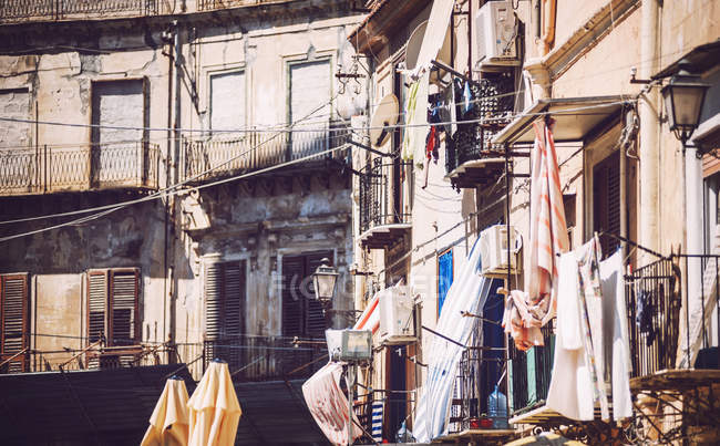 Detail of facades with clothes on balconies — Stock Photo