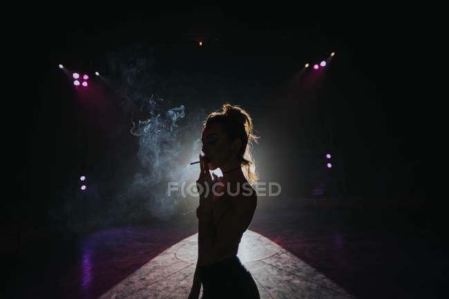 Силуэт женщины с сигаретой перед проектором — стоковое фото