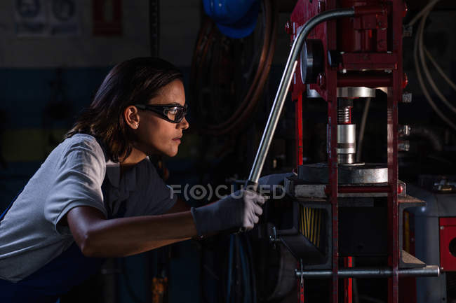 Side view of female mechanic in protective googles operating hydraulic press — Stock Photo