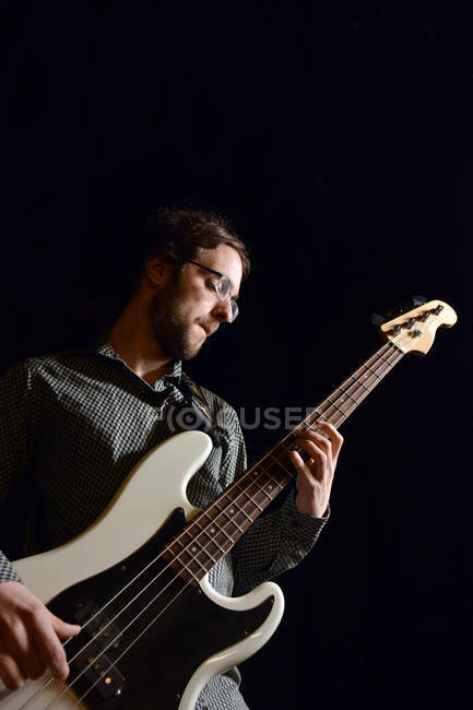Young man playing bass guitar — Stock Photo