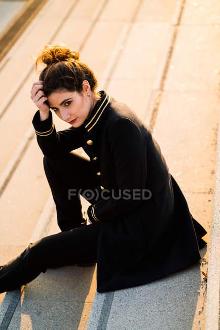 Femme en vêtements de sport assis sur les escaliers et regardant la caméra — Photo de stock