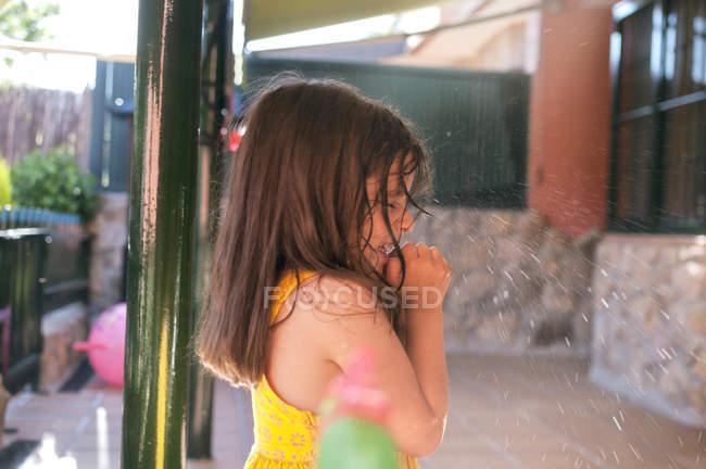 Vista laterale della piccola ragazza bruna nel cortile — Foto stock