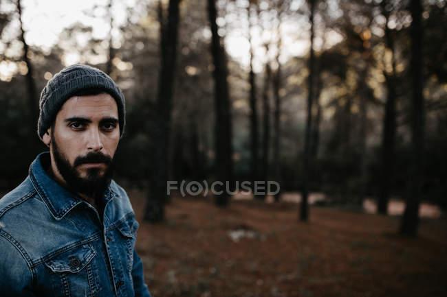 Бородач гуляет по лесу и смотрит в камеру. — стоковое фото