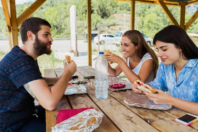 Amici allegri che mangiano durante il viaggio — Foto stock
