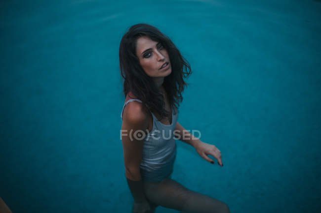 Portrait of brunette woman standing in transparent blue water in pool — Stock Photo