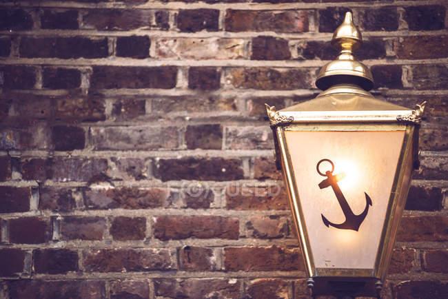 Fondo con textura de cultivo pared de ladrillo decorada con antigua linterna con el símbolo de ancla - foto de stock