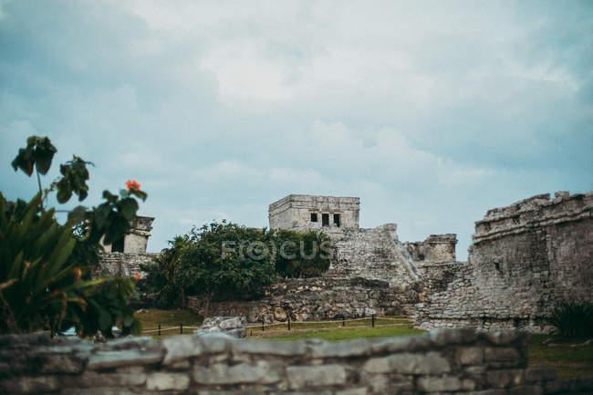 Низький кут зору камінь історичні руїни під похмуре небо у тропіках. — стокове фото