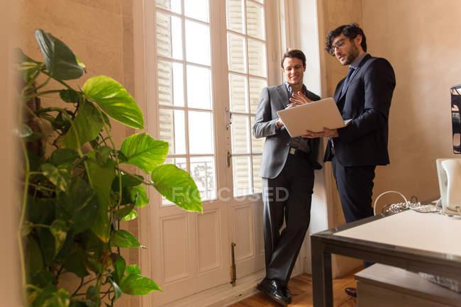Веселые люди в костюмах, обсуждение глядя на ноутбук — стоковое фото