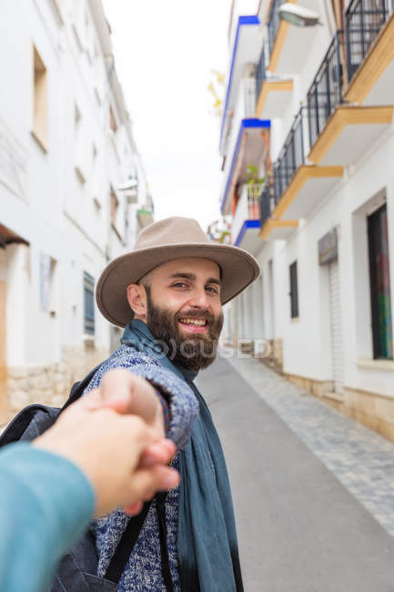 Bearded man looking at camera and gesturing follow me with photographer. — Stock Photo