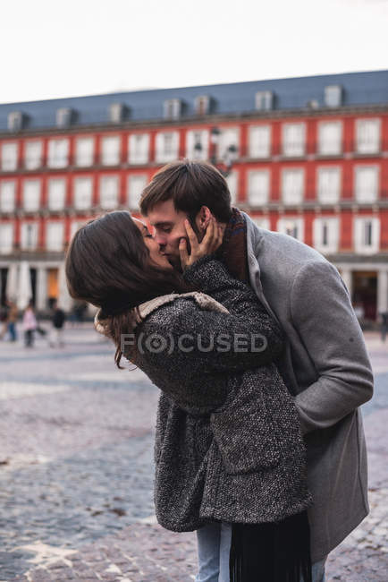 Young couple giving kiss to each other at town square — Stock Photo