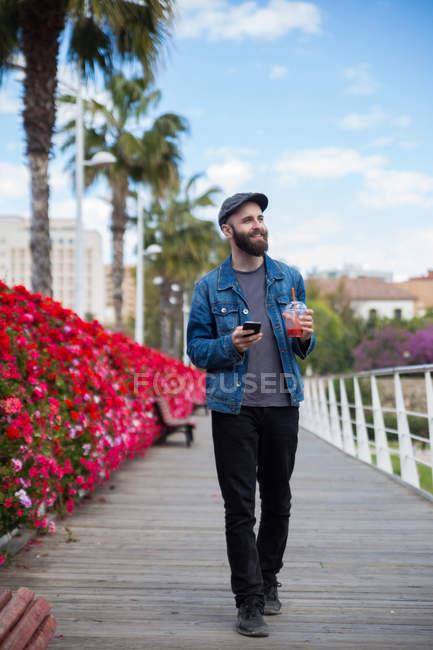 Retrato de hombre barbudo caminando con batido y smartphone en las manos y mirando a un lado - foto de stock