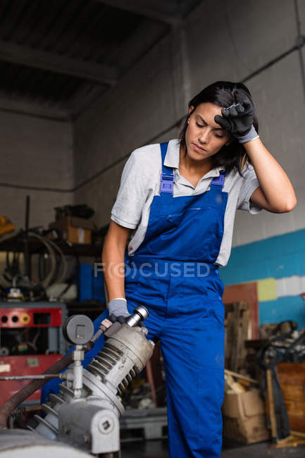 Tired female mechanic fixing compressor engine with wrench — Stock Photo