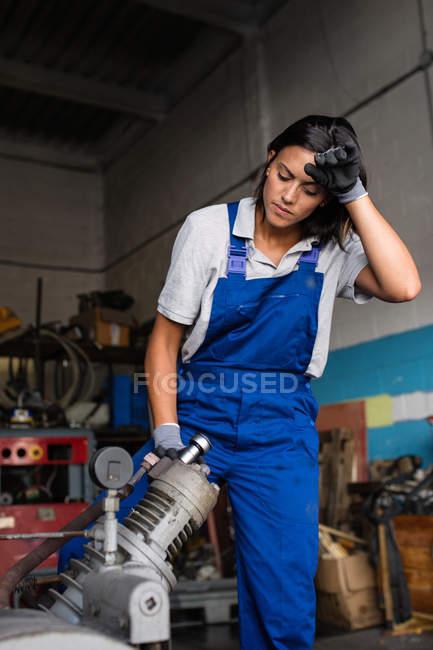 Cansado mujer mecanica motor de compresor fijación con una llave de - foto de stock