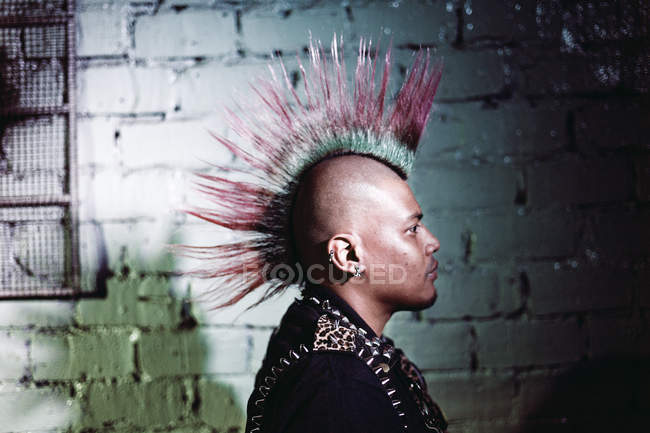 KAULA LUMPUR, MALASIA- 26 MART, 2016: Man in jacket with metal pikes wearing colorful mohawk on background of brick wall. — Stock Photo