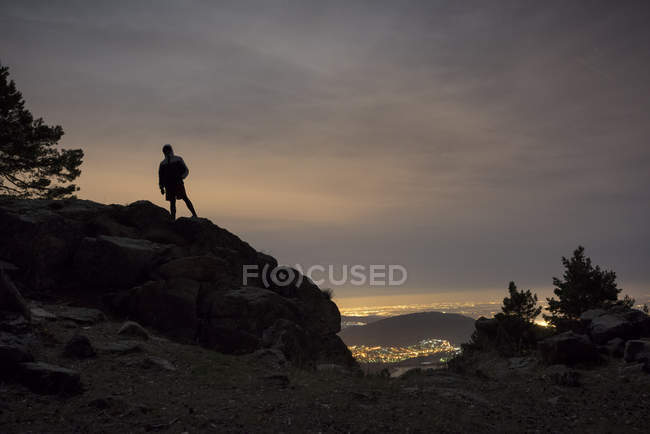 Silhouette of man on top of mountain against dusk sky — Stock Photo