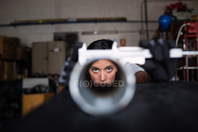 Portrait of female mechanic looking at camera through tube — Stock Photo