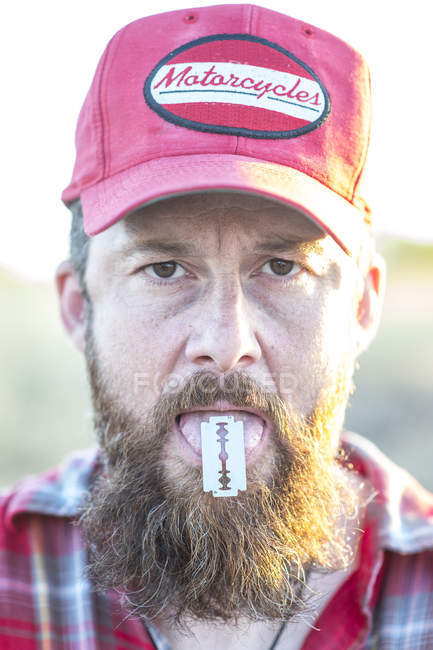 Portrait of bearded man in cap holding razor on tongue and looking at camera — Stock Photo