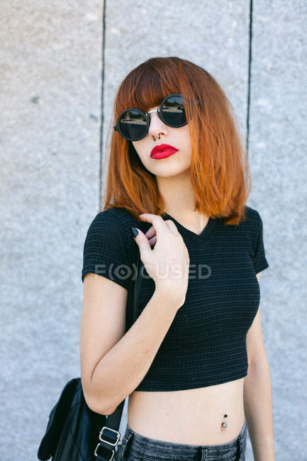 Fashion girl with red lips posing in sunglasses over grey wall — Stock Photo