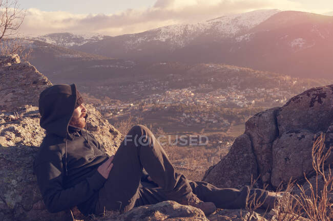 Man on top of mountain lying on the rock watching a nice sunrise in the sunny snowy mountain — Stock Photo