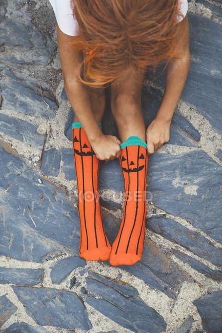 Girl adjusting orange socks — Stock Photo