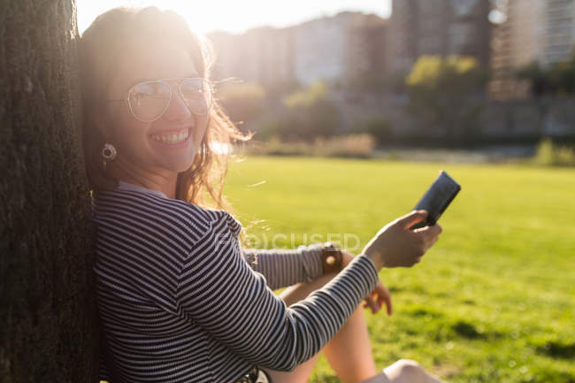 Усміхається жінка, сидячи на траві з смартфон, дивлячись на камеру — стокове фото
