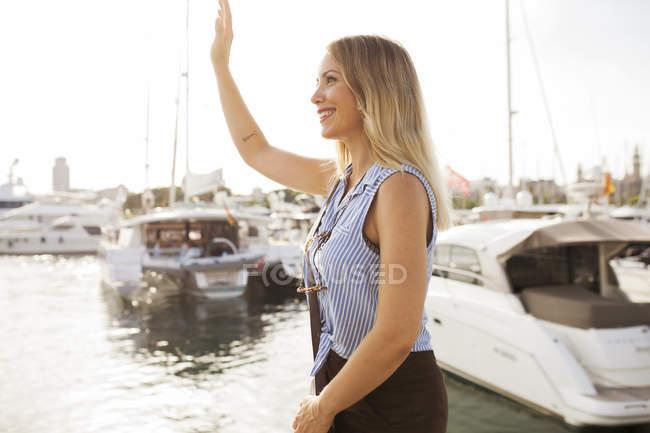 Mujer en muelle saludando mano - foto de stock