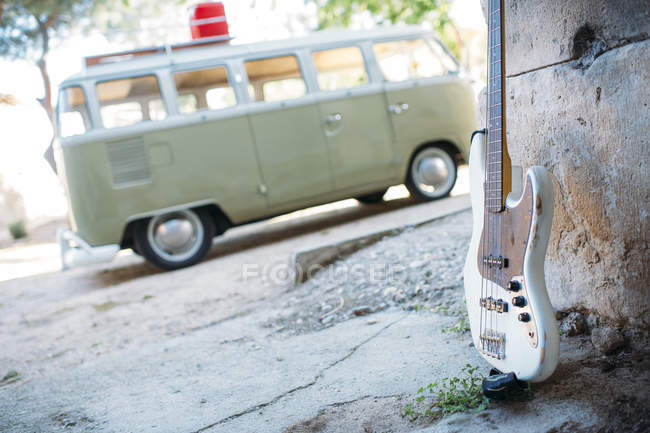 Shabby guitar leaned on wall on background of parked vintage van — Stock Photo