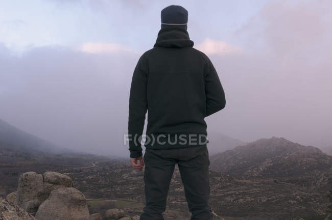 Rear view of man with hat in mountains on cloudy day — Stock Photo