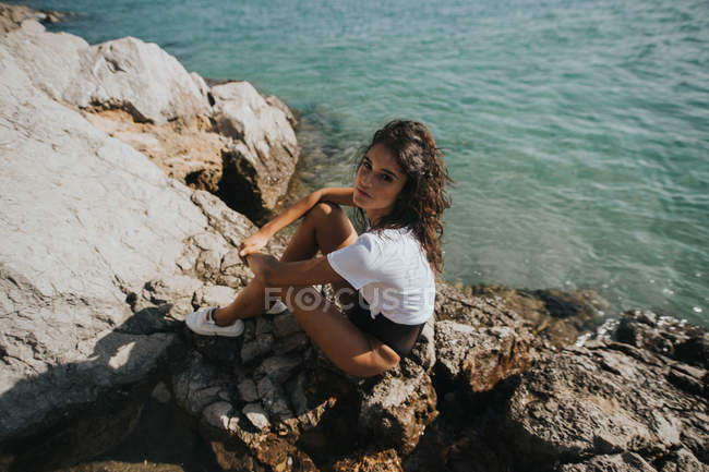 Портрет брюнетки, сидящей на скале у берега и смотрящей в камеру — стоковое фото