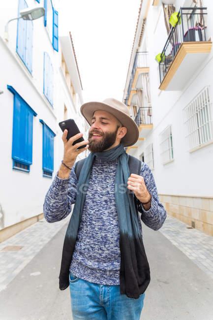 Bärtiger Mann mit Hut mit Sprachsuche mit Smartphone während des Gehens in der Straße. — Stockfoto