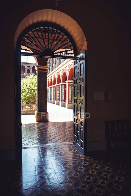 View to sunlit arched passage seen through doorway — Stock Photo