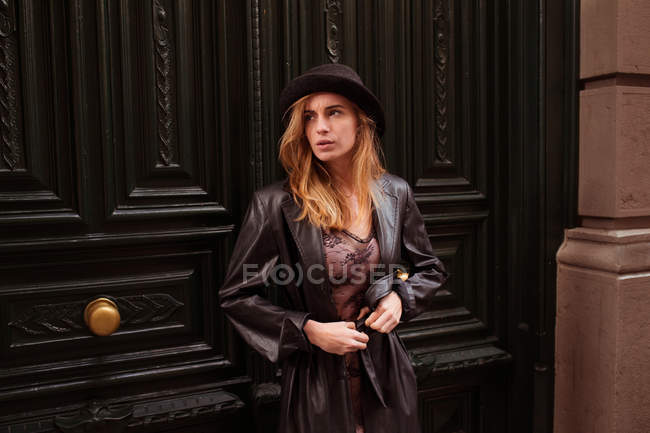 Young girl in hat looking away against ornate doors — Stock Photo