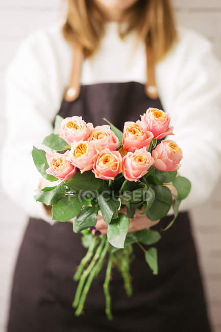 Close-up of female florist holding bunch of fresh pink roses — Stock Photo