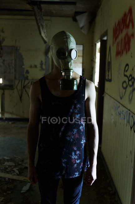 Homme au masque de gaz marchant à la maison abandonnée — Photo de stock