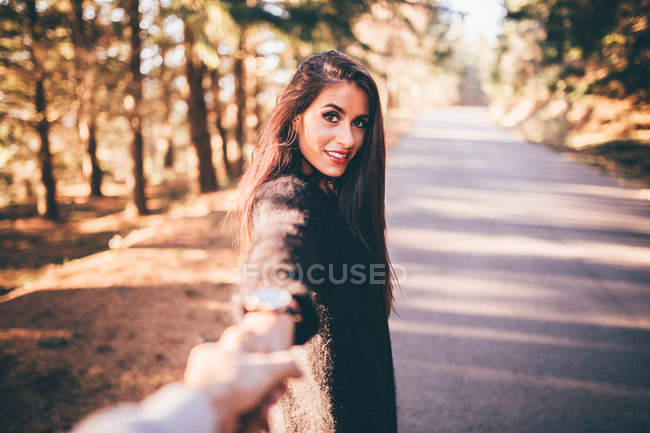 Брюнетка смотрит на камеру и жестикулирует в парке — стоковое фото