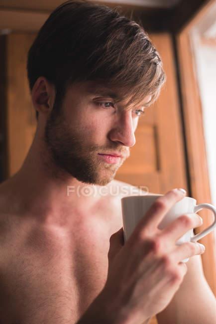 Замислений людина тримає чашку кави і, дивлячись — стокове фото