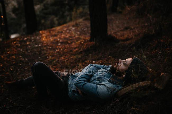 Seitenansicht einer Person, die im Herbst im Wald auf dem Boden liegt. — Stockfoto